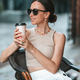Beautiful woman having breakfast at outdoor cafe. Happy young urban woman drinking coffee - PhotoDune Item for Sale