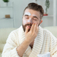 Bearded guy applying facial cream in front of mirror Skin care and spa for man concept - PhotoDune Item for Sale