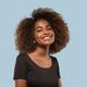 Beautiful african woman black t-shirt portrait afro haircut Color background. Blue - PhotoDune Item for Sale