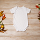 White baby short sleeve bodysuit mockup with snowberry and fall leaves - PhotoDune Item for Sale