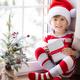 Happy child wearing Christmas pajamas sitting on windowsill - PhotoDune Item for Sale