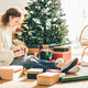 Woman wrapping Christmas gifts at home. Packing the Christmas presents. - PhotoDune Item for Sale