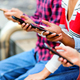 Friends sitting on bench and browsing smartphones in daytime - PhotoDune Item for Sale