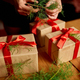Hands of cropped unrecognisable woman packing Christmas present - PhotoDune Item for Sale