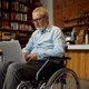 Adult disabled man in wheelchair using laptop - PhotoDune Item for Sale
