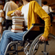Disabled female student holds stack of books - PhotoDune Item for Sale