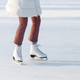 Closeup of woman legs in red checked trousers on skates on an open skating rink. Winter hobby - PhotoDune Item for Sale