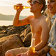Man Drinking Beer By Smiling Girlfriend At Beach - PhotoDune Item for Sale