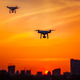 Two modern Remote Control Air Drones Fly with action cameras in dramatic orange sunset sk - PhotoDune Item for Sale