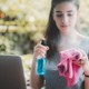 Young female vlogger with mic and dumbbells holding a cloth and spray bottle to clean laptop - PhotoDune Item for Sale
