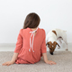 Rear view of a little girl in a red polka dot dress sitting on the floor next to her beloved dog - PhotoDune Item for Sale
