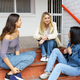 Multi-ethnic group of three friends sitting on street steps talking - PhotoDune Item for Sale