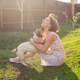 Slender cute young woman plays with her beloved funny dog in the yard on a sunny summer day. Lovely - PhotoDune Item for Sale