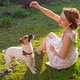 Laughing positive young woman in dress plays with her beloved restless dog sitting in the yard of a - PhotoDune Item for Sale
