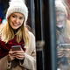 Portrait of beautiful happy young woman calling on smartphone over christmas light in winter evening - PhotoDune Item for Sale