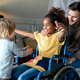 Happy multiethnic family. Smiling little girl with disability in wheelchair at home - PhotoDune Item for Sale