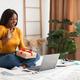 Black Female Video Calling On Laptop Holding Gift Sitting Indoor - PhotoDune Item for Sale