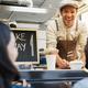 Hispanic man serving take away food inside food truck - Focus on chef face - PhotoDune Item for Sale