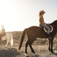 Young couple riding horses doing excursion at countryside during sunset time - Focus on woman - PhotoDune Item for Sale
