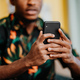 Portrait of unrecognizable young man using smartphone, sitting on sofa at home, social networks - PhotoDune Item for Sale