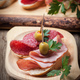 Tapas with sliced sausage, salami, olives and parsley on a wooden table. - PhotoDune Item for Sale