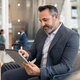 Mature businessman using digital tablet at departure lounge at the airport - PhotoDune Item for Sale