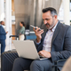 Businessman working with phone and laptop at the airport - PhotoDune Item for Sale