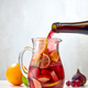 red wine pouring into jug of cutted fruits - PhotoDune Item for Sale