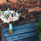 Beautiful wedding bouquete of roses stands on wooden bench against brick wall background - PhotoDune Item for Sale