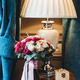 Beautiful wedding bouquet of roses stand on wooden desk in bride`s bedroom near lamp - PhotoDune Item for Sale