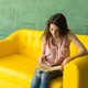 people, interior and education concept - young woman reading book on yellow sofa - PhotoDune Item for Sale