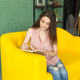 People, education and interior concept - Young woman sitting on a couch and reading a book - PhotoDune Item for Sale
