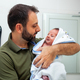 First bath of newborn baby boy. The baby is in the bathrobe in his father's arms. - PhotoDune Item for Sale