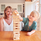 Mother And Daughter Having Fun Sitting At Table Playing Game Building Tower From Wooden Blocks - PhotoDune Item for Sale
