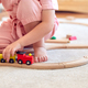 Close Up Of Young Girl At Home Playing With Wooden Train Set Toy On Carpet - PhotoDune Item for Sale