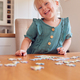 Portrait Of Young Girl Having Fun Sitting At Table At Home Doing Jigsaw Puzzle - PhotoDune Item for Sale