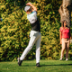 Golfing couple. Man teeing off with the driver, lady in the back, following the ball in flight - PhotoDune Item for Sale