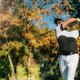 Golfer teeing off with the driver golf club on a beautiful autumn day - PhotoDune Item for Sale