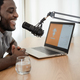 African man recording a podcast using microphone and laptop from his home studio - PhotoDune Item for Sale