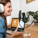 Mature woman recording a podcast using microphone and laptop from her home studio - PhotoDune Item for Sale