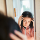 Portrait of a beautiful young woman examining her scalp and hair in front of the mirror, - PhotoDune Item for Sale