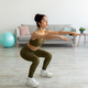 Full length of sporty young Indian woman doing squats at home - PhotoDune Item for Sale