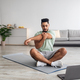 Athletic young Arab man doing yoga in front of laptop during home workout, copy space - PhotoDune Item for Sale