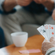 Senior friends sit at a coffee table and play cards - PhotoDune Item for Sale