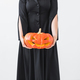 Halloween concept - Anonymous witch with pumpkin Jack-o'-lantern on light background - PhotoDune Item for Sale