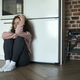 Sad and thoughtful young caucasian woman sitting on floor in the kitchen - PhotoDune Item for Sale