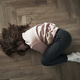 Top view of young caucasian woman lying on floor and having strong stomachache - PhotoDune Item for Sale