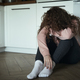 Broken young caucasian woman  with hidden face sitting on floor in the kitchen - PhotoDune Item for Sale