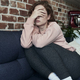 Depressed young caucasian woman sitting on sofa with eyes covered - PhotoDune Item for Sale