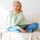 Smiling senior woman looking at camera and relaxing on sofa in daytime at home - PhotoDune Item for Sale